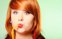 Redhair girl holding sweet food jelly candy on green. Stock Image
