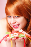 Redhair girl holding sweet food jelly candy on pink. Stock Photo