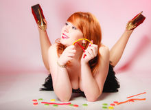 Redhair girl holding sweet food jelly candy on pink. Royalty Free Stock Images