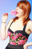 Redhair girl holding sweet food lollipop candy on blue. Stock Photos