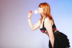 Redhair girl holding sweet food lollipop candy on blue. Stock Images
