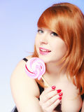 Redhair girl holding sweet food lollipop candy on blue. Stock Image