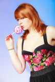 Redhair girl holding sweet food lollipop candy on blue. Royalty Free Stock Photo