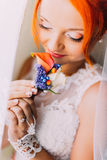 Redhair girl in a wedding dress holds boutonniere and smiles. Studio background Stock Image