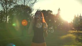 Redhair imbirowa kobieta bawić się z mydlanymi bąblami, plenerowymi mieć zabawę zbiory