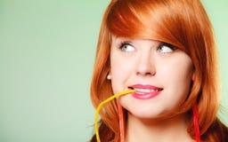 Redhair-Mädchen, das süße Lebensmittelgeleesüßigkeit auf Grün hält Stockfotografie