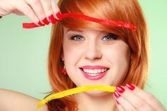 Redhair-Mädchen, das süße Lebensmittelgeleesüßigkeit auf Grün hält Stockfotos