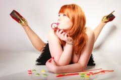 Redhair-Mädchen, das süße Lebensmittelgeleesüßigkeit auf Grau hält Stockbild