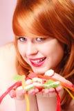 Redhair-Mädchen, das süße Lebensmittelgeleesüßigkeit auf Rosa hält Stockfoto