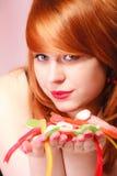 Redhair-Mädchen, das süße Lebensmittelgeleesüßigkeit auf Rosa hält Lizenzfreie Stockfotos