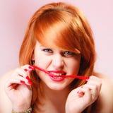 Redhair-Mädchen, das süße Lebensmittelgeleesüßigkeit auf Rosa hält Lizenzfreies Stockbild