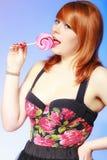 Redhair-Mädchen, das süße Lebensmittellutschersüßigkeit auf Blau hält Stockfotos
