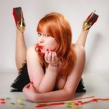 Redhair-Mädchen, das süße Lebensmittelgeleesüßigkeit auf Grau hält Lizenzfreies Stockfoto