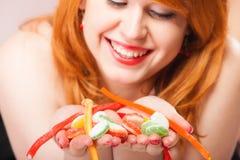 Redhair-Mädchen, das süße Lebensmittelgeleesüßigkeit auf Rosa hält Lizenzfreies Stockfoto