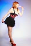 Redhair-Mädchen, das süße Lebensmittellutschersüßigkeit auf Blau hält Stockfoto