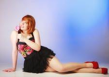 Redhair-Mädchen, das süße Lebensmittellutschersüßigkeit auf Blau hält Stockbild