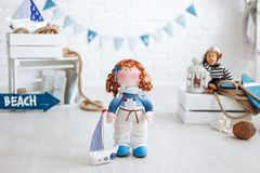 A redhair sailor doll and a ship with a sail standing on a white floor. Handmade stock photos