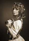 有看照相机的枪的美丽的redhair steampunk女孩 老 免版税库存照片