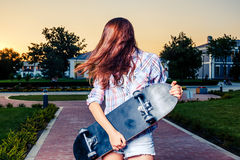 Redhair teenager dancing with skateboard in hands Stock Photos