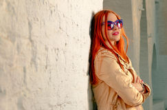 Redhair woman looking away happy. Trendy girl posing near white brick wall in casual clothes and fashionable 60th style sunglasses Stock Photography