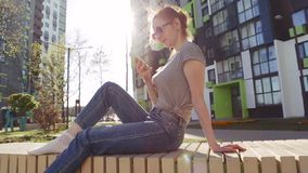 Redhair woman watching video on smartphone sitting outdoor stock video footage