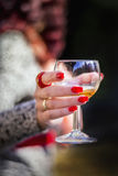 Redhair womans hand with red nails and rings giving a wineglass Stock Photos