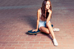 Redhair women is sitting on skateboard outdoors Stock Photography