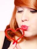 Redhaired девушка держа поцелуй красной влюбленности сердца дуя красный цвет поднял Стоковая Фотография