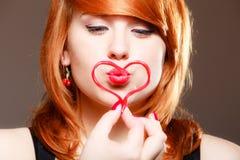 Redhaired девушка держа поцелуй красной влюбленности сердца дуя красный цвет поднял Стоковая Фотография RF