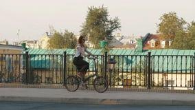 Redhaired Frau, die ein Fahrrad in der Stadt auf Hintergrundgebäude und Dachhaus reitet stockfotografie