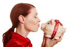 Redhaired Frau, die piggy küßt stockfotos