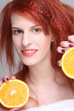 Redhaired Frau mit orange Hälfte Stockbild