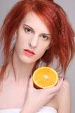Redhaired Frau mit orange Hälfte in ihrer Hand Lizenzfreies Stockbild