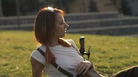 Redhaired Frauenradfahrer, der auf grünem Rasen im Sommerpark stillsteht stock footage