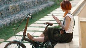 Redhaired Frauenradfahrer, der selfie am Handy mit Fahrrad macht Frauenradfahren lizenzfreie stockfotografie
