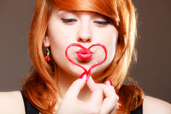 Redhaired girl holding red heart love blowing kiss. Valentines day. Royalty Free Stock Photography