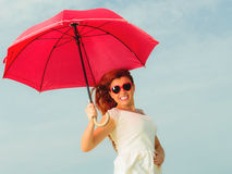 Redhaired girl jumping with umbrella on beach. Holidays, vacation travel and freedom concept. Beautiful redhaired happy girl jumping with red umbrella on beach Stock Photography