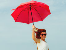 Redhaired girl jumping with umbrella on beach. Holidays, vacation travel and freedom concept. Beautiful redhaired happy girl jumping with red umbrella on beach Royalty Free Stock Photos