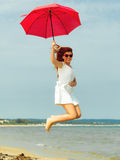 Redhaired girl jumping with umbrella on beach. Holidays, vacation travel and freedom concept. Beautiful redhaired happy girl jumping with red umbrella on beach Royalty Free Stock Images