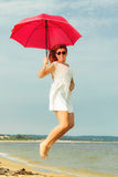Redhaired girl jumping with umbrella on beach. Holidays, vacation travel and freedom concept. Beautiful redhaired happy girl jumping with red umbrella on beach Stock Photo