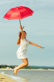 Redhaired girl jumping with umbrella on beach Royalty Free Stock Photography