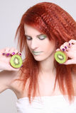 Redhaired girl with kiwi over white Stock Photos