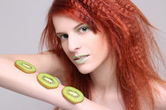 Redhaired girl with kiwi slices on her hand Royalty Free Stock Photo