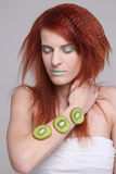 Redhaired girl with kiwi slices on her hand Royalty Free Stock Photos