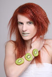 Redhaired girl with kiwi slices on her hand Stock Image