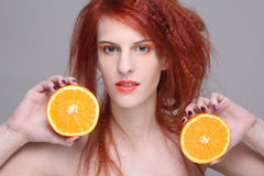 Redhaired girl with orange half. Beautiful redhaired woman with orange half Royalty Free Stock Images
