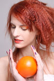 Redhaired girl with orange in her hands. Attractive redhaired girl with orange in her hands over grey Royalty Free Stock Image