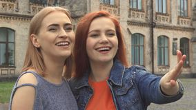Two girls Laughing at something in front of them. Redhaired girl points at something. Friends laughing, looking at each other and discussing. Girls standing stock video