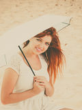 Redhaired girl sitting under umbrella on beach. Stock Photo