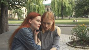Two girls talking on the same phone. Redhaired girl talking on phone while blonde seats by. Then they share the phone to have a talk. They listen, discuss and stock video footage